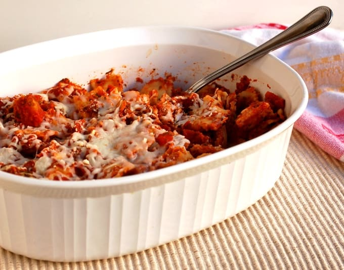 Cheesy ravioli with marinara sauce and melted mozzarella cheese in white casserole dish with serving spoon.