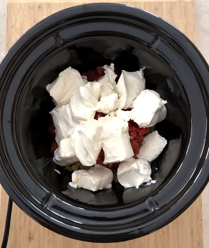 Adding cubed cream cheese to tomatoes and corn in crock pot.