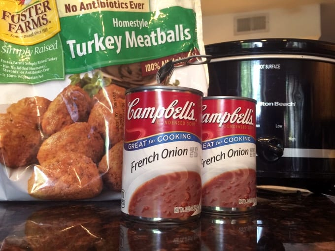 Package of frozen turkey meatballs with two cans of Campbell's French Onion soup for making Slow Cooker French Onion Meatballs.