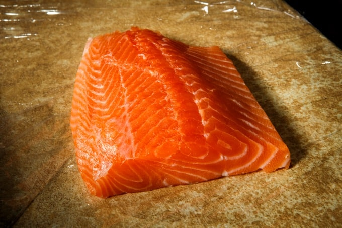 big piece of peeled raw salmon fillet lies on counter covered with food film