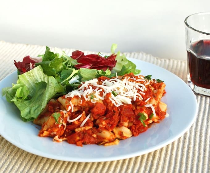 Ravioli with marinara sauce and shredded mozzarella with green salad on white dinner plate with glass of red wine.