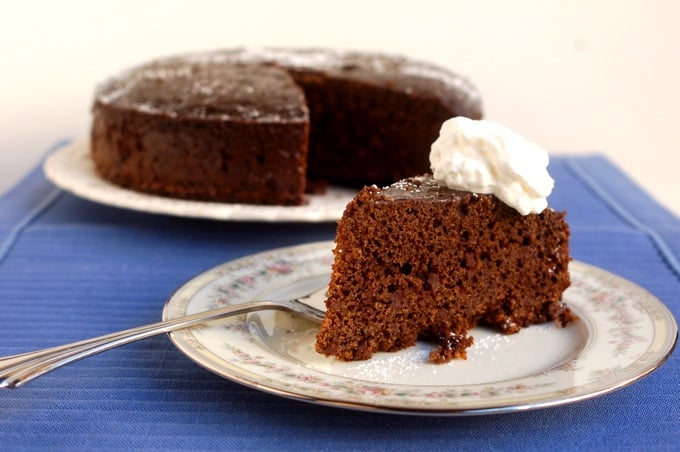 Slice of Easy Crock Pot Gingerbread topped with whipped cream on a small plate in front of the whole gingerbread cake
