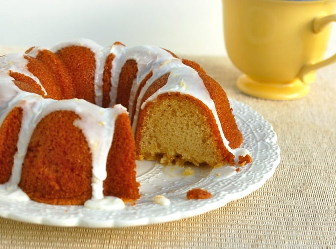 Slow cooker lemon bundt cake with icing on white cake plate.
