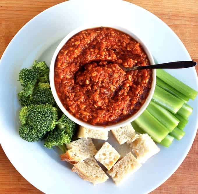 Bowl of pizza dip in bowl with broccoli florets, celery and bread cubes for dipping