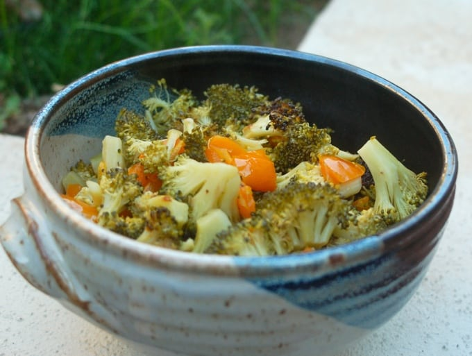 Roasted Broccoli and orange bell pepper in a blue ceramic bowl