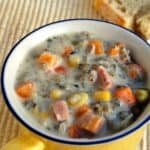 Creamy ham and wild rice soup in yellow mug with crusty bread and spoon.