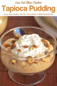 Tapioca pudding with whipped topping and chopped pistachios in small glass dessert dish with a spoon.