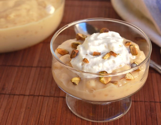 Slow cooker tapioca pudding with whipped topping and chopped pistachios in small glass dessert dish with spoon.
