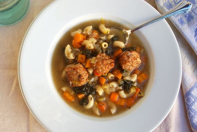 Slow Cooker Easy Italian Wedding Soup in white bowl with spoon.
