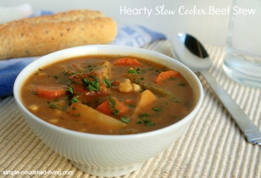 Hearty Slow Cooker Beef Stew in white bowl with baguette in background