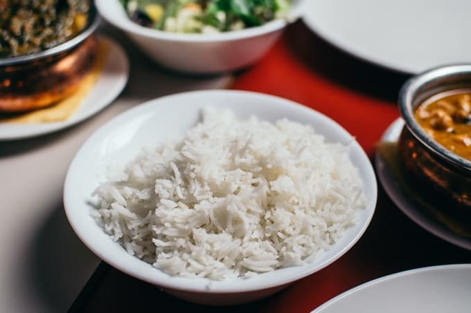 Bowl of cooked white rice with various side dishes