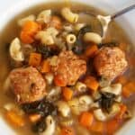 Slow Cooker Italian Wedding Soup in white bowl with spoon from above.