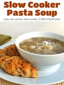 Bowl of pasta soup with grated Parmesan cheese and two fresh croissants