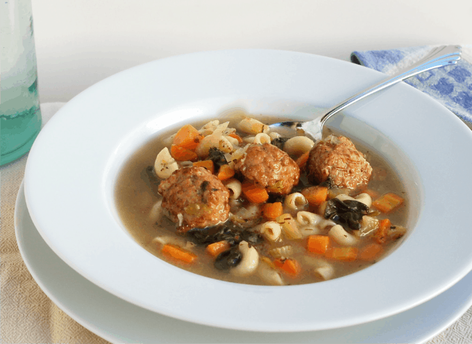 Italian Wedding Soup with three turkey meatballs in white bowl with spoon.