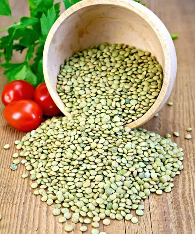 Dry green lentils in a tipped over wooden bowl with parsley and red tomatoes on a wooden table
