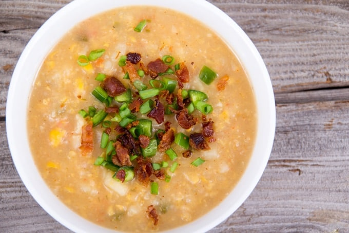 Homemade corn chowder soup bowl topped with crumbled bacon and sliced green onion