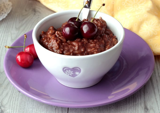 Chocolate rice pudding topped with fresh cherries in white bowl on small purple plate.