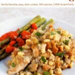 Crock pot chicken and stuffing with asparagus on white dinner plate.
