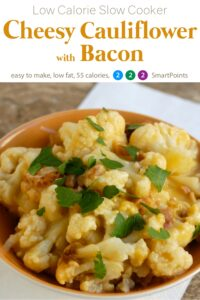 Slow cooker cheesy cauliflower with bacon in orange dish garnished with chopped parsley.