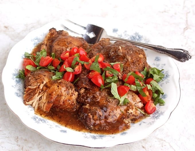 Balsamic Chicken Thighs garnished with chopped tomatoes and basil on a white platter with serving fork