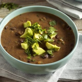 Homemade Black Bean Soup in a Green Bowl with Avocado and Cilantro