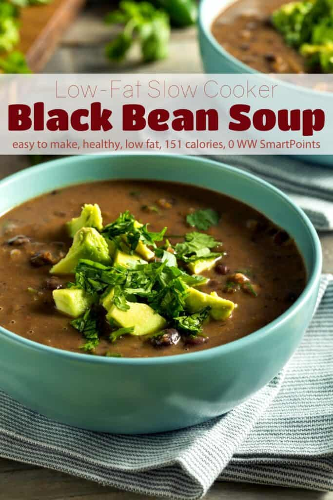 Black bean soup in blue bowl garnished with chopped avocado and cilantro.