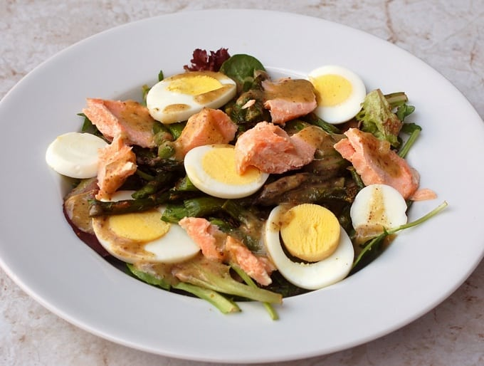 Mixed greens salad with salmon, asparagus and sliced boiled egg on white plate