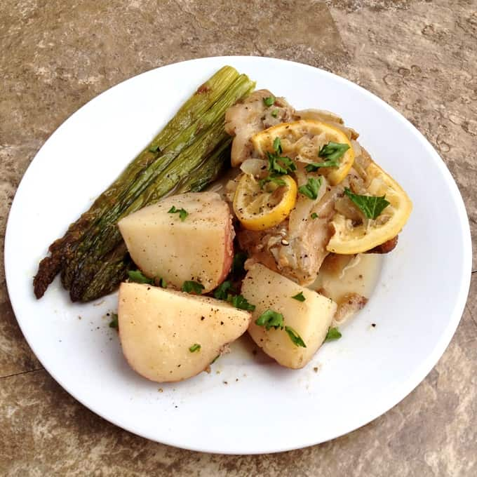 Slow Cooker Lemon Chicken and Potatoes on a white dinner plate with asparagus.
