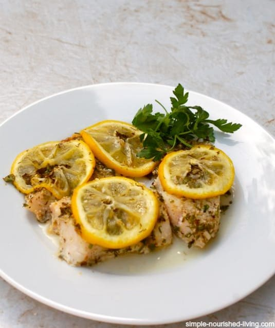 Easy Baked Fish with Lemon and Herbs on white plate