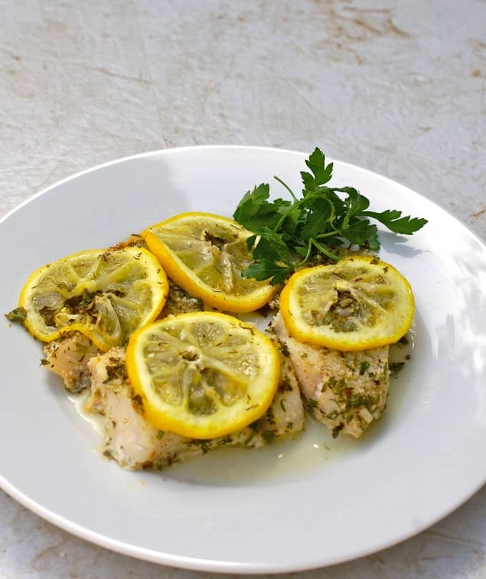 Baked Fish topped with slices of lemon and fresh herbs on white dinner plate