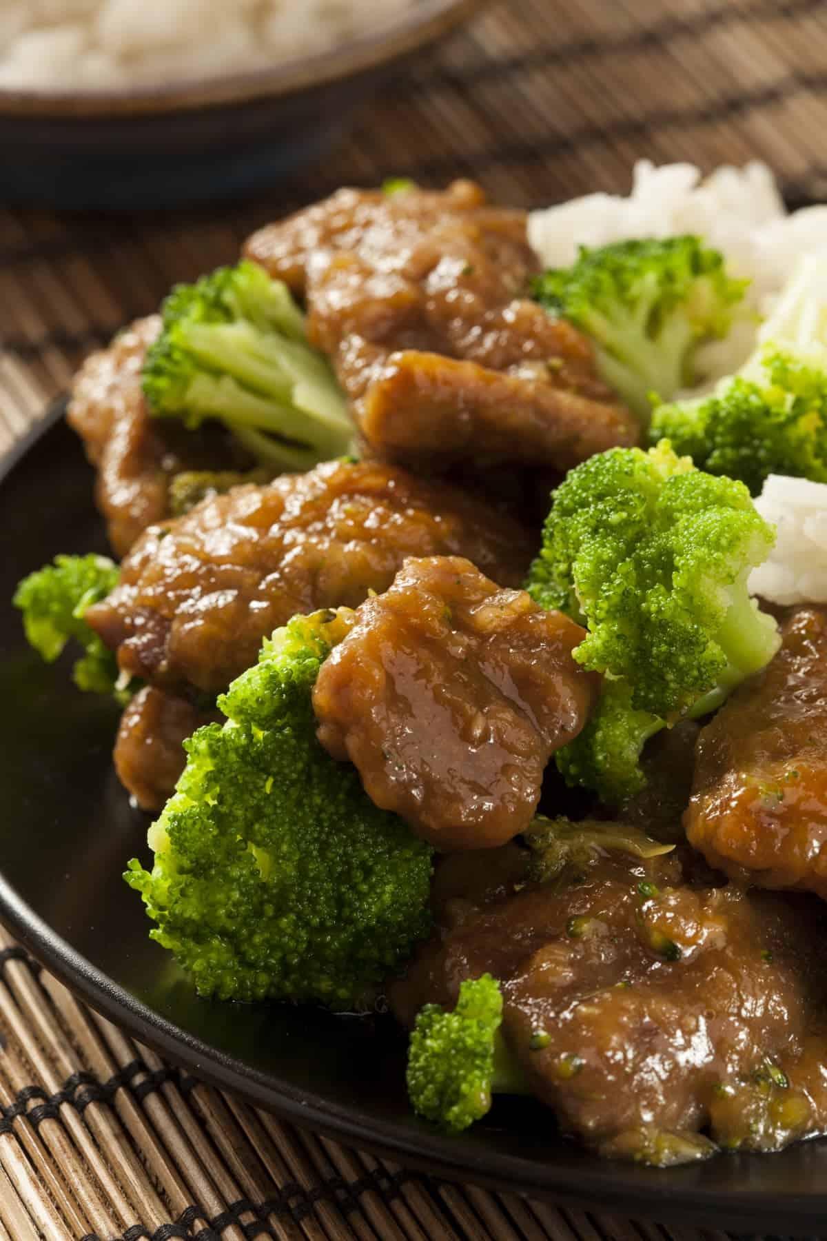 Beef with Broccoli and white rice on dark plate on bamboo mat.