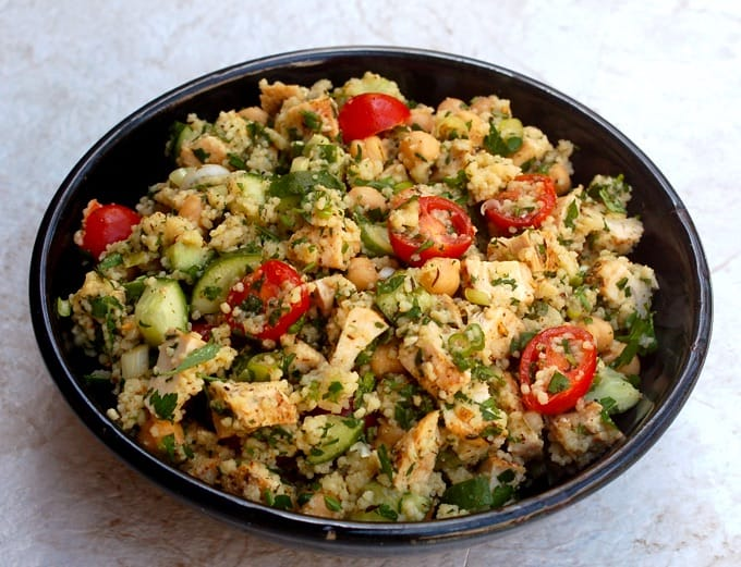 Mediterranean Salad with Couscous, Chicken, Tomatoes, Cucumber and Chickpeas in a blue serving dish