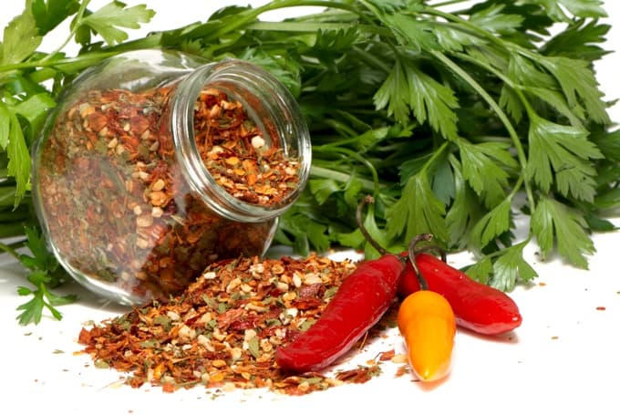 Cajun spices in glass jar spilled on table with parsley and chili peppers