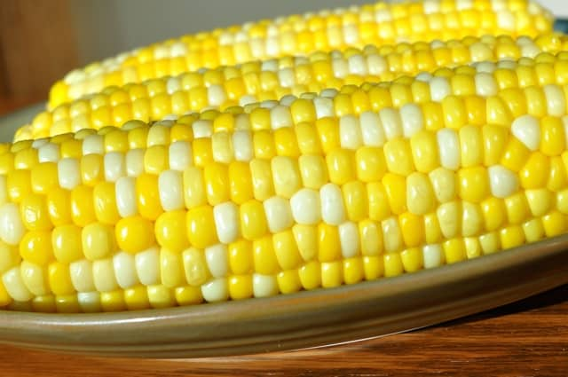 Corn on the cob sitting on brown plate up close.