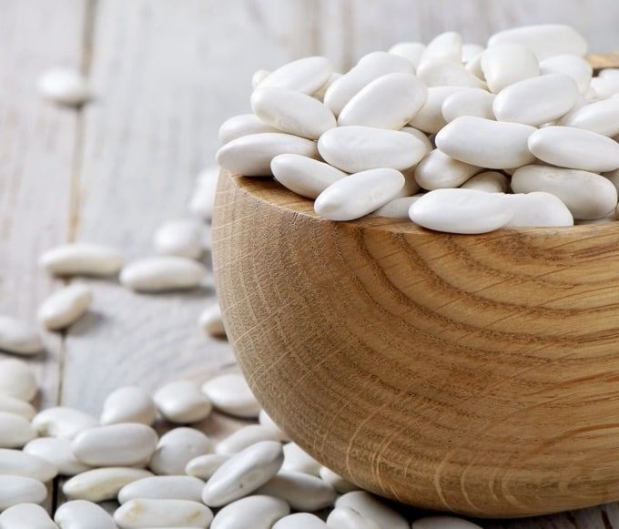 Dry white beans in a brown wood bowl on a wooden table