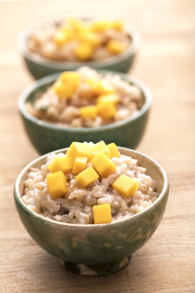 Three small bowls of rice pudding topped with chopped mango.
