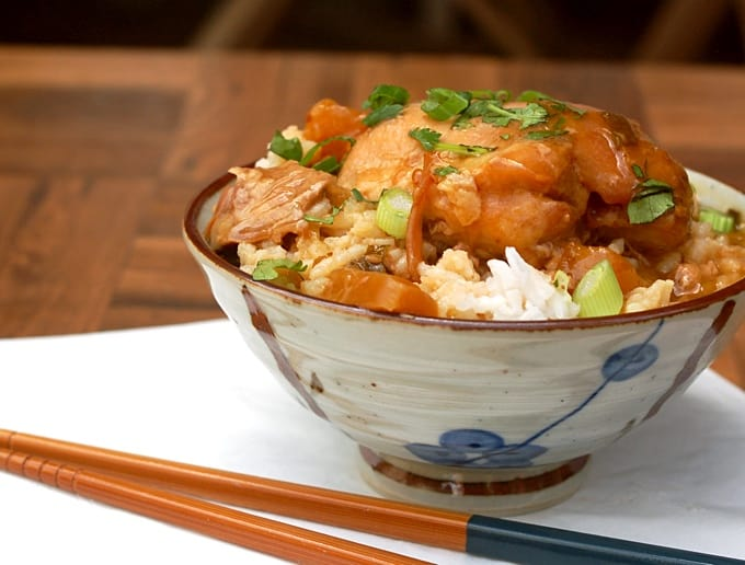 Chicken teriyaki with pineapple over white rice in ceramic bowl with chop sticks.
