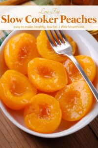 Slow cooker peaches in white serving dish with fork.