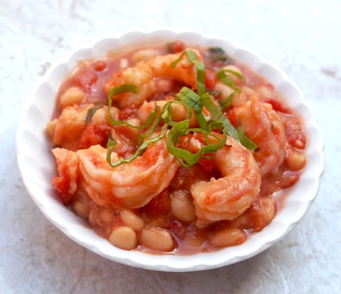 White beans with shrimp garnished with sliced fresh basil in white bowl.