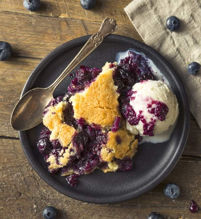 Mixed berry cobbler with scoop of vanilla ice cream and spoon on black plate with blueberries scatter on wood table.