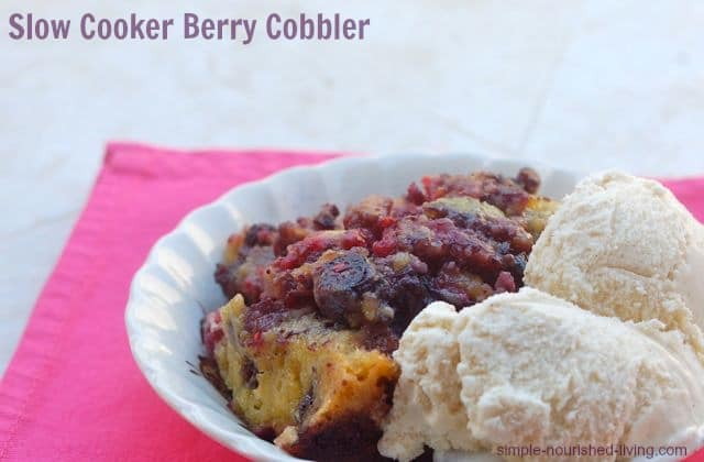Slow Cooker Berry Cobbler in a bowl with ice cream pink mat