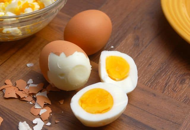 Three hard-boiled eggs on a wood table, one egg has it's shell, one egg shell is partially peeled, and one egg is cut in half showing its yellow yolks
