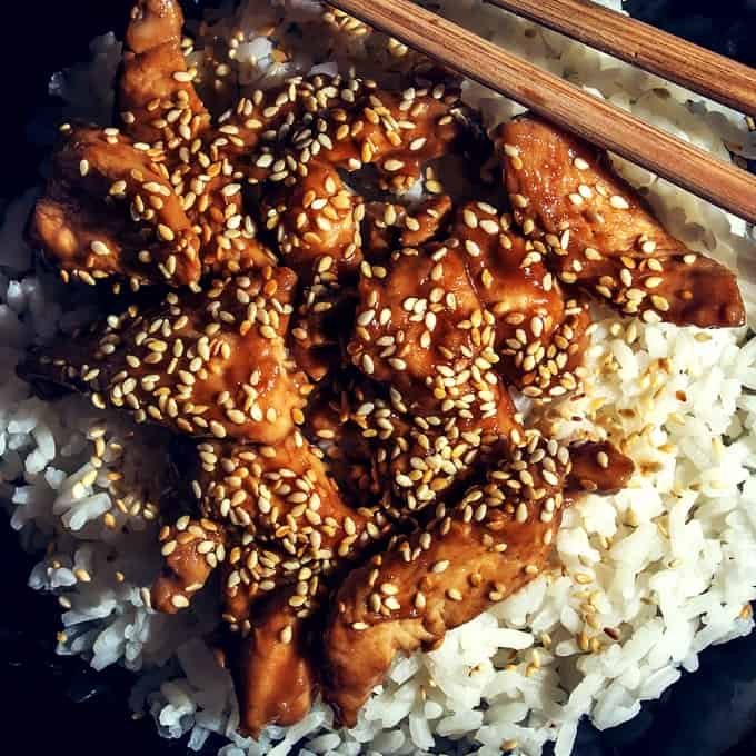 Slow Cooker Sesame Chicken over white rice with chopsticks.