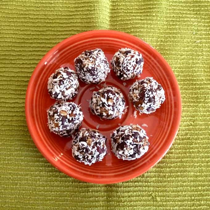 No-bake cherry date nut balls on an orange plate from overhead.