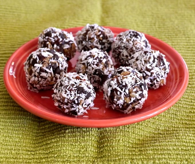 Gluten-free cherry date nut bites rolled in shredded coconut on an orange plate.