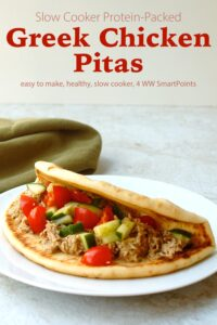 Slow Cooker Greek Chicken Pita with fresh chopped tomatoes and cucumbers on a white plate.