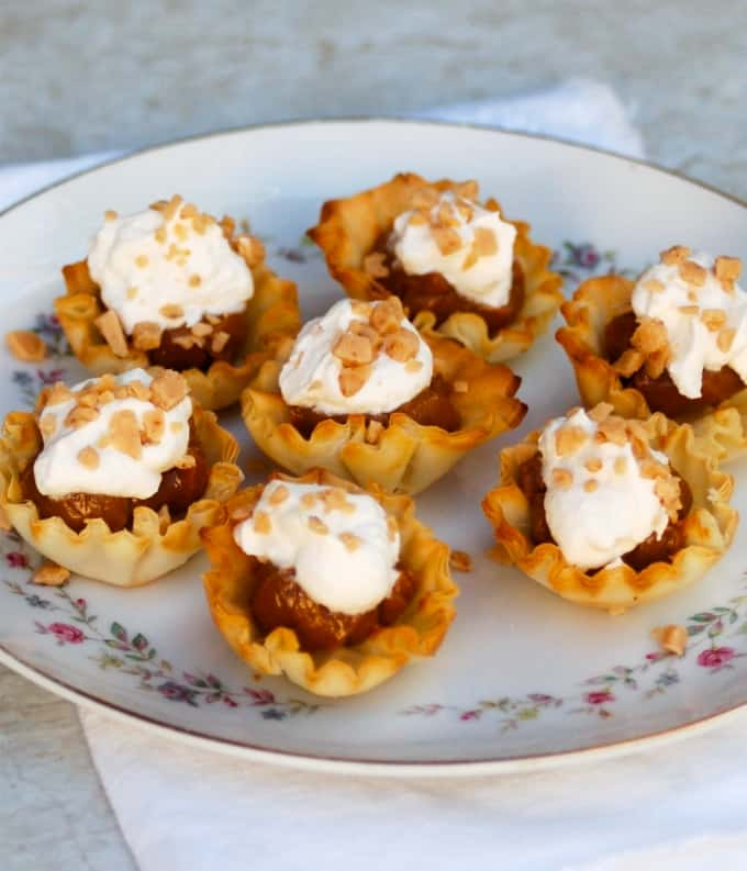 4-Ingredient Dulce De Leche Tartlets garnished with whipped topping and Heath bits on serving plate.