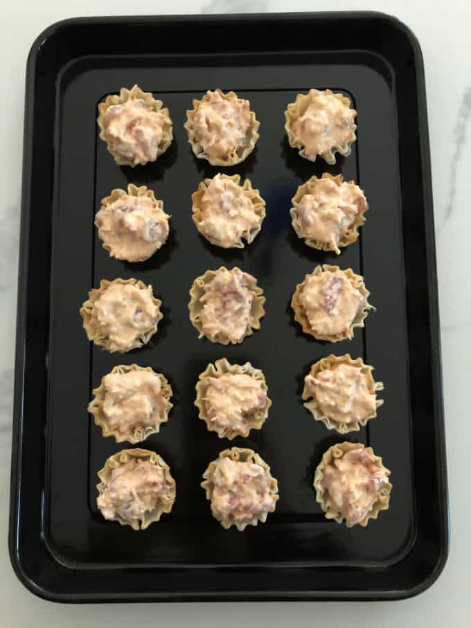 Baked mini buffalo chicken bites in baking pan.