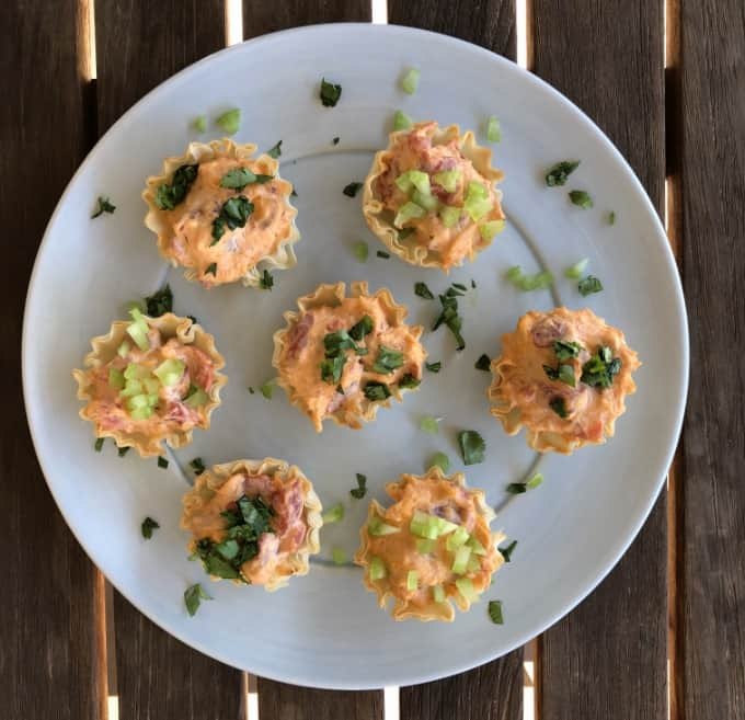 Mini buffalo chicken bites topped with chopped celery and cilantro on blue plate.