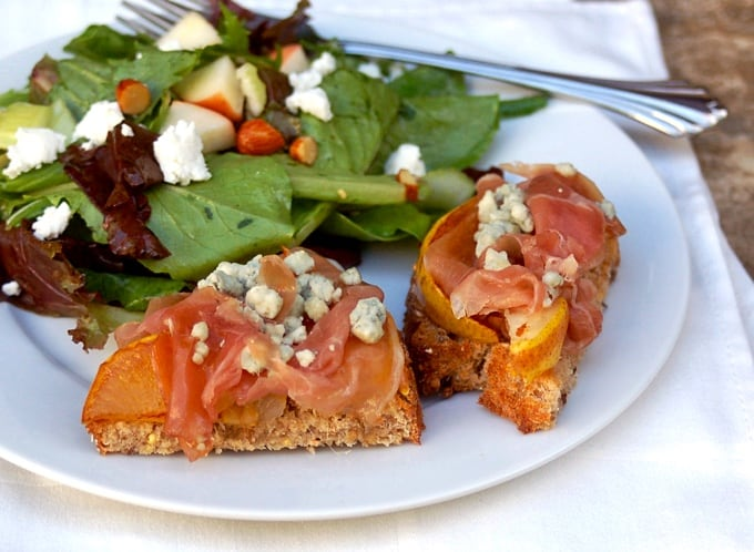 Open-Face Prosciutto, Pear and Blue Cheese Sandwich with mixed greens salad on white plate with a fork.